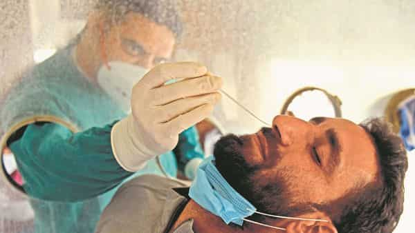 A health worker collects a nasal swab sample from a man to test for the covid-19 coronavirus in a mobile testing van in Amritsar (Photo: AFP)