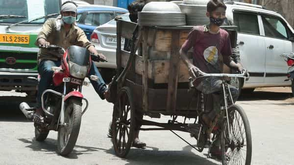 A rickshaw cart is nudged along by a motorcyclist as work activity resumes at Wazirpur Industrial area amid the unlocking process of Covid-19 lockdown, in New Delhi. (PTI)