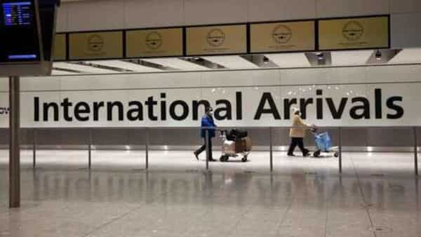 FILE - In this Tuesday, Jan. 26, 2021 file photo, arriving passengers walk past a sign in the arrivals area at Heathrow Airport in London. (AP)