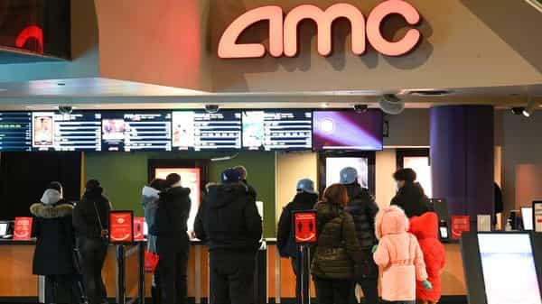 People line up for movie tickets at a reopened AMC theater in New York