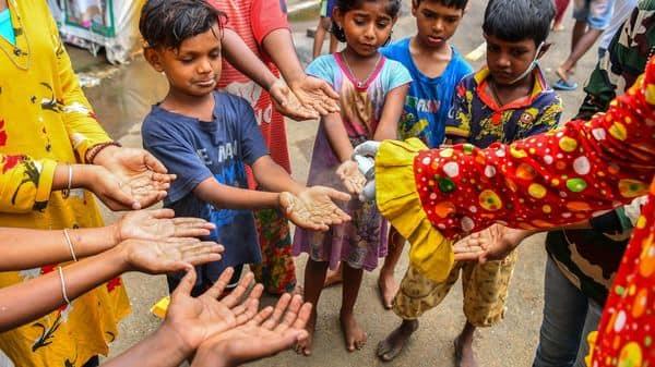 Social worker volunteer Ashok Kurmi, dressed as a clown sprays hand sanitiser as he teaches to children how to follow the Covid-19 coronavirus safety protocols inside a slum area in Mumbai on June 2, 2021 (AFP)