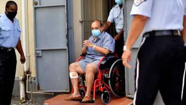 Mehul Choksi exits in a wheelchair the magistrate's court in Roseau, Dominica, Friday, June 4, 2021.  (AP)