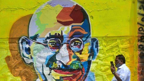 A man walks past a graffiti wall of Mahatma Gandhi at P. D'Mello Road in Mumbai, India,  (HT)
