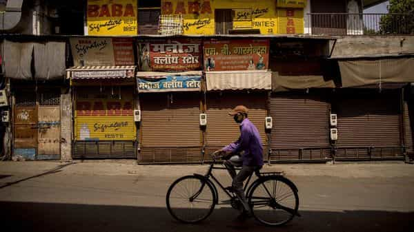 A cyclist rides past closed stores in a deserted market area during lockdown restrictions in Agra, Uttar Pradesh. (Bloomberg)