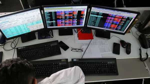 FILE PHOTO: A broker reacts while trading at his computer terminal at a stock brokerage firm (REUTERS)