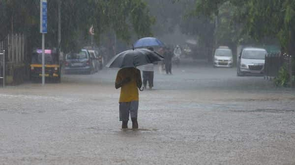 People make their way through the waterlogged road during heavy rains (HT PHOTO)