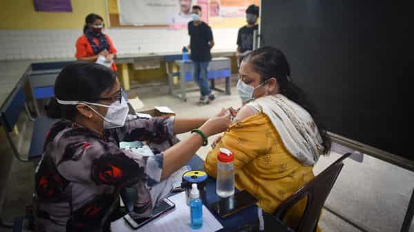 A health worker seen giving a jab of Covid vaccine to a beneficiary inside a vaccination centre in New Delhi.