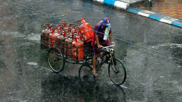 A worker carries LPG cylinders on a tricycle. (PTI)