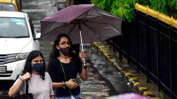 People hold their umbrellas as they walk in rain at CSMT, in Mumbai, India (Anshuman Poyrekar/HT PHOTO)