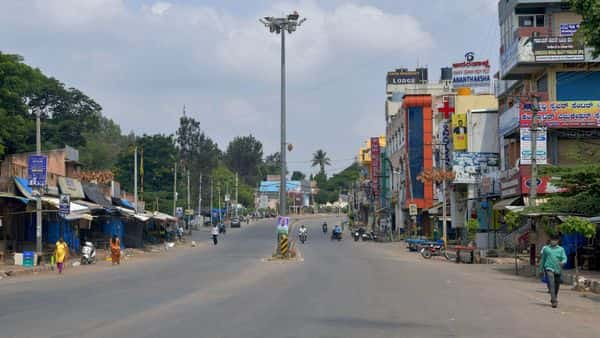People are seen on a partially deserted road after a lockdown was imposed in Karnataka (AFP)