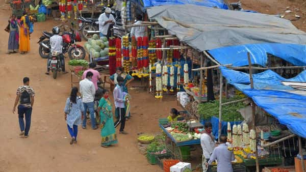 People buy fruits and vegetables from the hawkers as the state authorities lifted travel restrictions eased the lockdown norms that were imposed earlier to curb the spread of Covid-19 in Bangalore. (AFP)