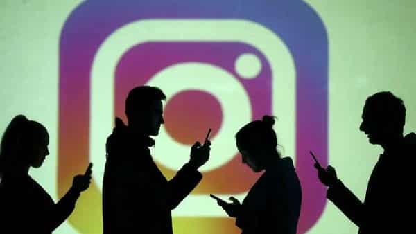 Silhouettes of mobile users are seen next to a screen projection of Instagram logo. (File photo)