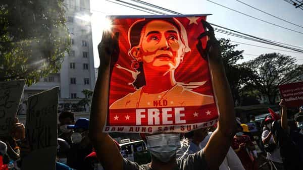 A protester holds up a poster featuring Aung San Suu Kyi during a demonstration against the military coup  (AFP)