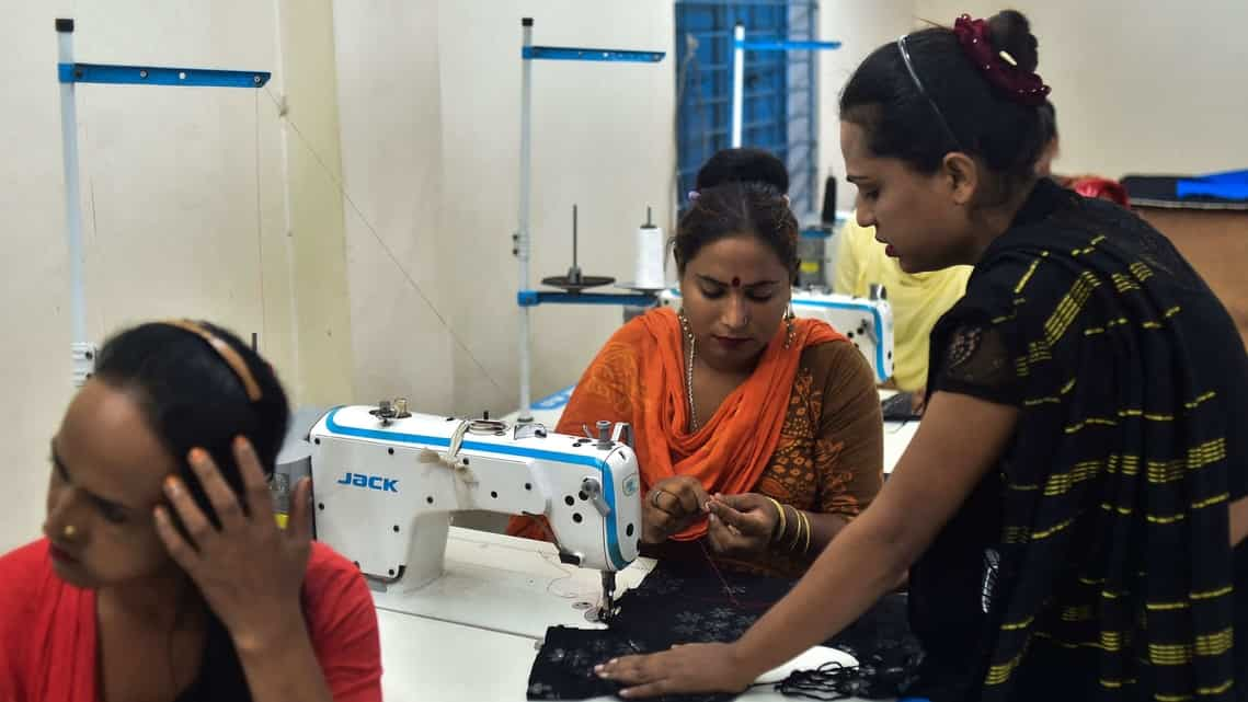 Apon Akther (standing), who identifies as a third gender, is the owner of small garment factory in Dhaka, Uttoron Fashion And Shopno Tailors.