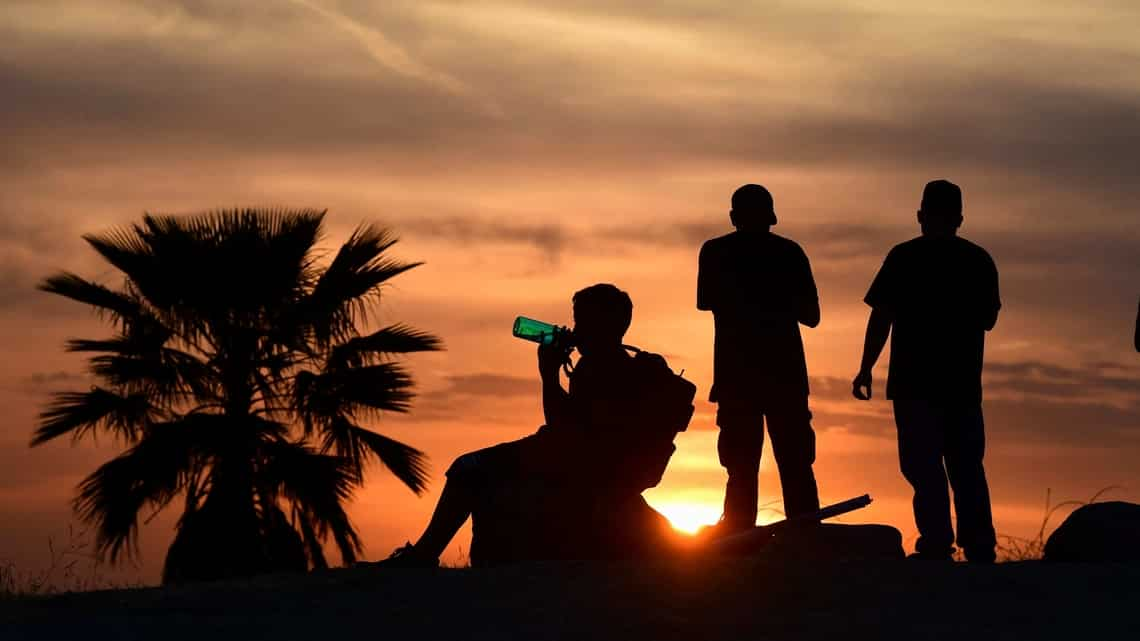 People view the sun set as a child drinks from a water bottle on June 15, 2021 in Los Angeles, California as temperatures soar in an early-season heatwave.