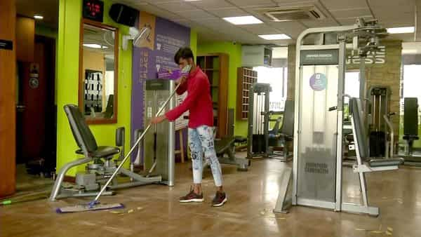 A worker cleans gym as it prepares to reopen with 50% capacity after relaxation from COVID-19 restrictions, in Delhi on Sunday.