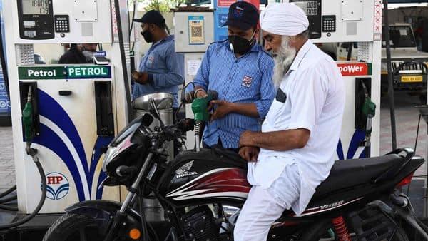 A fuel pump attendant fills a motorbike petrol tank at a gas station (AFP)
