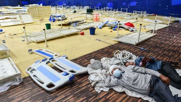 New Delhi: Workers take rest near dismantled beds of a Covid care centre at CWG village near Akshardham in New Delhi (PTI)