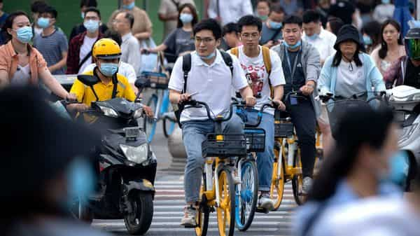 People ride bicycles across an intersection during rush hour in Beijing. (AP)