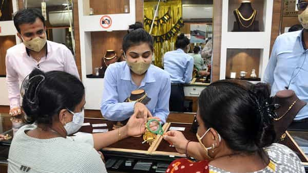 A jeweller shows Trademarks to customers as of now Trademarks are compulsory on Gold Jewelry, at Jewellery Shops, in Surat on Wednesday. (ANI Photo)