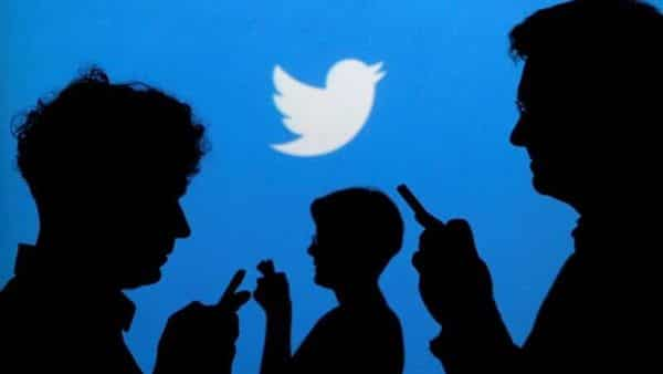 People holding mobile phones are silhouetted against a backdrop projected with the Twitter logo in this illustration picture. (REUTERS)