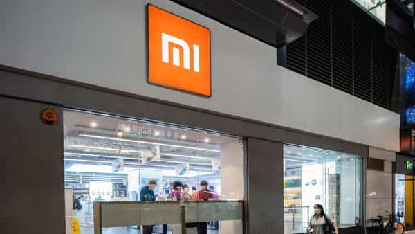 A pedestrian wearing a protective mask walks past a Xiaomi Corp. store in Hong Kong, China. (Bloomberg)