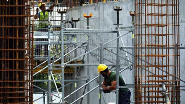 Construction workers fit steel reinforcement rods. (Bloomberg)
