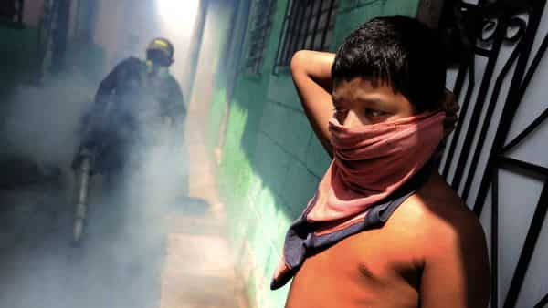A child protects himself outside his house as sanitation workers fumigate the area to eliminate vector-borne pathogens. (AFP)
