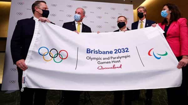 (L-R) Lord Mayor of Brisbane Adrian Schrinner, Australian Senator Richard Colbeck, President of Australian Olympic Committee John Coates, three time Olympic gold medalist James Tomkins and Premier of Queensland Annastacia Palaszczuk, attend a press conference after Brisbane was announced as the 2032 Summer Olympics host city during the 138th IOC Session at Hotel Okura in Tokyo on July 21, 2021. (AFP)