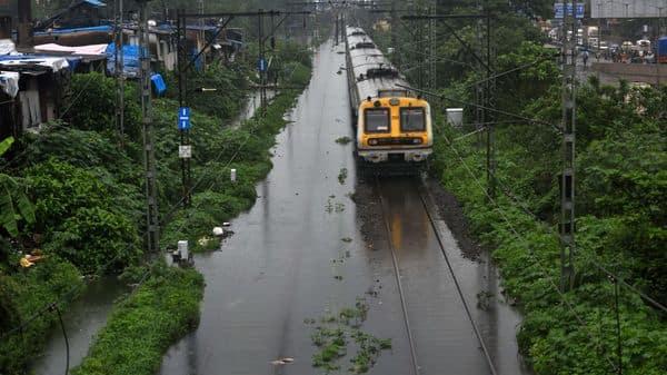 A local train wades through a waterlogged railway track due to heavy downpour of rain near Tilak Nagar, in Mumbai (HT)