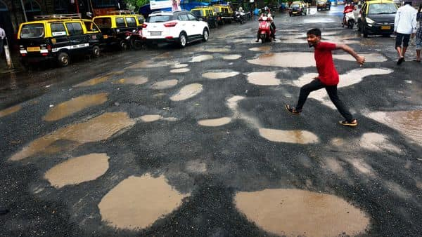 Mumbai: Pothole-ridden road outside Reay Road railway station causes inconvenience to motorists and pedestrians (Satish Bate/HT PHOTO)
