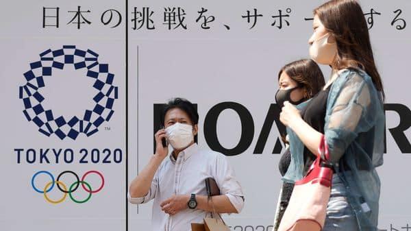 People walk past an Tokyo Olympics logo in Tokyo. (AP)
