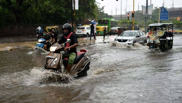 Vehicles make their way through flooded roads during heavy rainfall, in New Delhi on Tuesday. (ANI Photo)