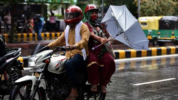 A pillion rider on a bike tries to hold an umbrella to protect herself from rainfall, in New Delhi on Wednesday. ((ANI Photo))