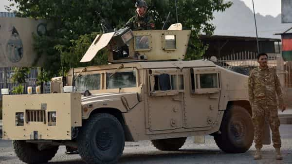 Afghan security personnel stand guard on a Humvee vehicle along a road in Kandahar. (AFP)