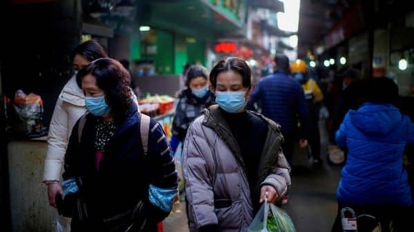 People wearing face masks walk on a street market, following an outbreak of the coronavirus disease (COVID-19) in Wuhan, Hubei province, China (REUTERS)