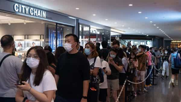 People queue to collect shopping coupons at a mall in Hong Kong. (AFP)