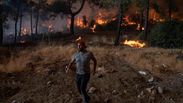 A man walks ahead of a wildfire in Mugla, Marmaris district, as the European Union sent help to Turkey and volunteers joined firefighters in battling a week of violent blazes that have killed eight people. (AFP)