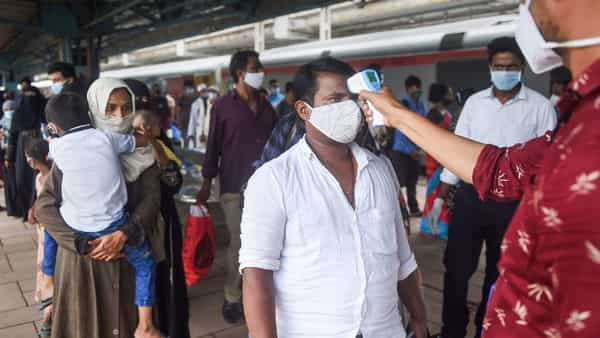 Mumbai: A BMC health worker does the thermal screening of a passenger for COVID-19 test, at Dadar railway station. (PTI)