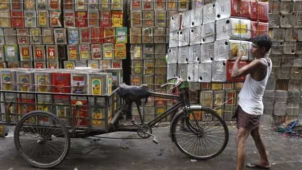A man loads empty containers of edible oil onto a tricycle (REUTERS)