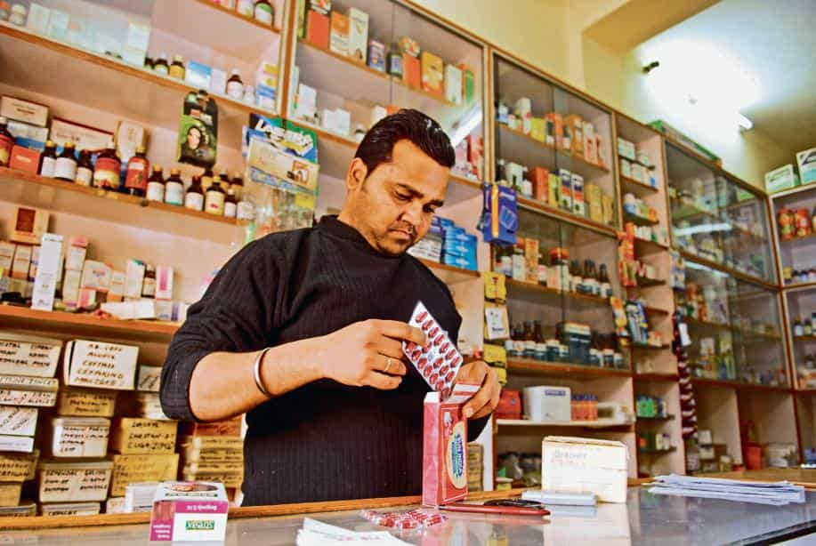 A pharmacy owner checks his stock of medicine; The Indian regulator needs to weigh the risks and benefits of contaminated drugs before allowing them to be sold freely.