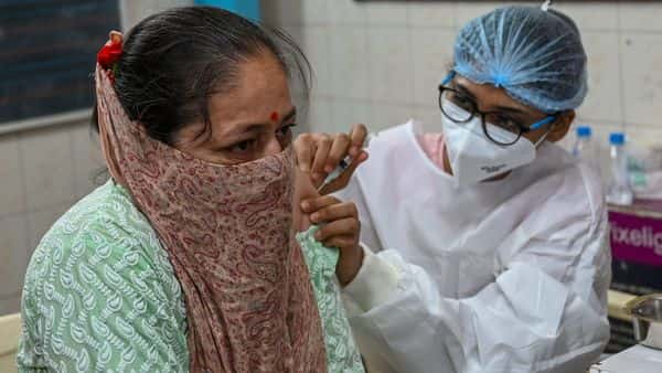 A health worker inoculates a woman with the dose of Covaxin vaccine against the Covid-19 coronavirus at a temporary vaccination centre set up in a school in Mumbai. (AFP)