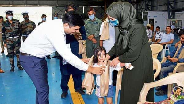 An official welcomes the child of an Indian diplomat who was evacuated from Kabul after the city was seized by the Taliban (Photo: AFP)