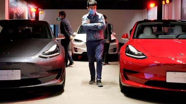 A man walks by Tesla Model 3 sedans and Tesla Model X sport utility vehicle at a Tesla showroom