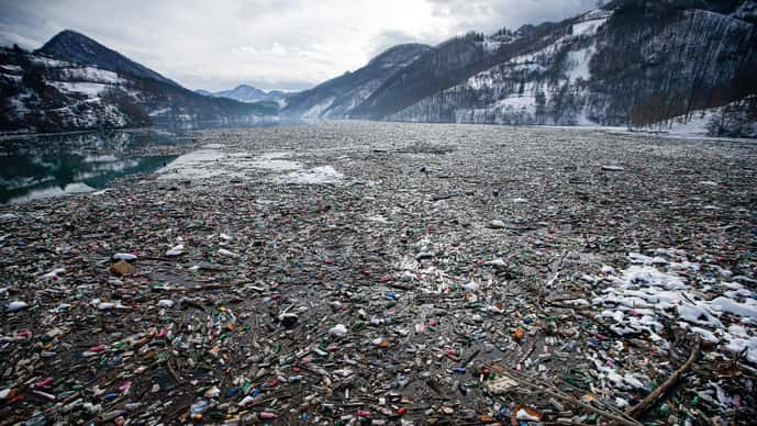 In this January 2021 file photo, plastic bottles and other garbage floats in the Potpecko lake near Priboj, in southwest Serbia. There is increasing international alarm over the sheer volumes of fossil-fuel based plastics entering the environment.