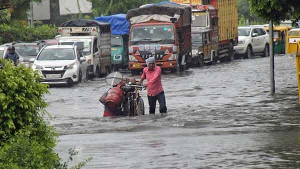 Commuters move through a waterlogged road amid rainfall, at ITO, in New Delhi on Saturday. (ANI Photo)