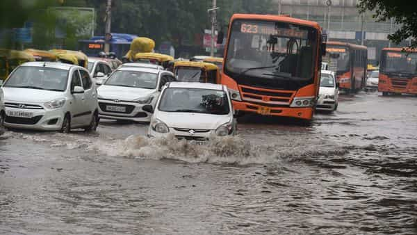 Commuters wade through a waterlogged area following heavy rains in New Delhi (PTI)