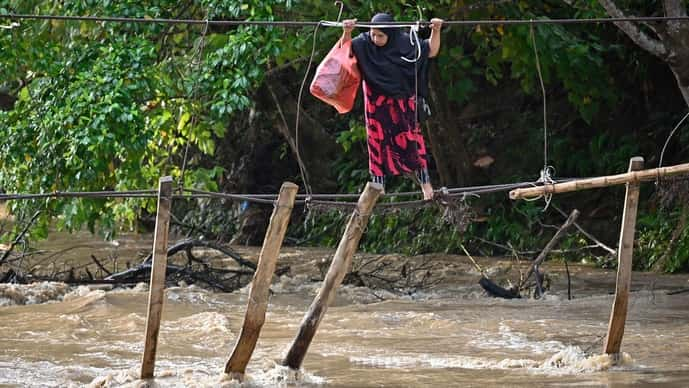A woman crosses a river using the remains of a bridge, swept away during flooding the previous year, at Malela village in Luwu Regency, South Sulawesi on September 13. As many as 216 million people could move within their own countries due to slow-onset climate change impacts by 2050.