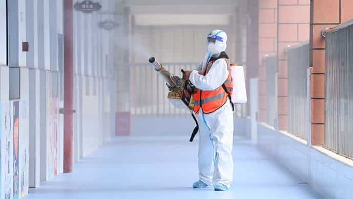 This photo taken on August 25, 2021 shows a staff member spraying disinfectant at a primary school ahead of the new semester in Wuhan, in China's central Hubei province. (Photo by STR / AFP)