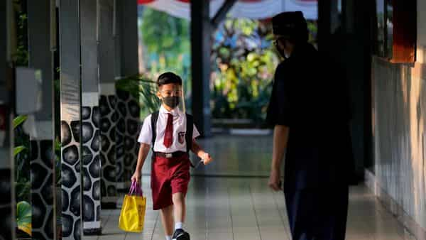 Staff greets a student during the first day of school reopening at an elementary school in Jakarta, Indonesia, Monday, Aug. 30, 2021. Authorities in Indonesia's capital kicked off the school reopening after over a year of remote learning on Monday as the daily count of new COVID-19 cases continues to decline. (AP Photo/Dita Alangkara) (AP)